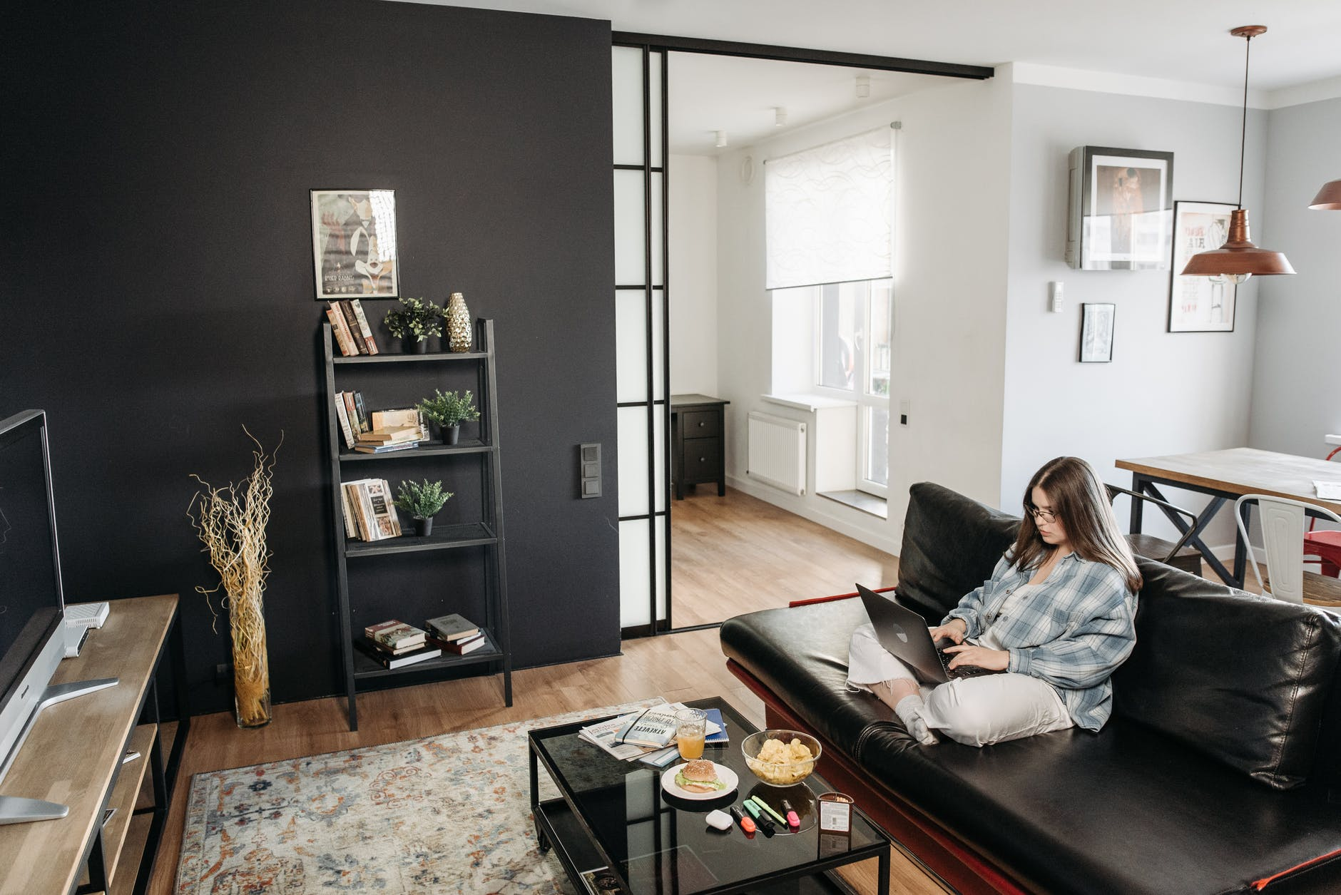 woman using her laptop while sitting on a black leather sofa